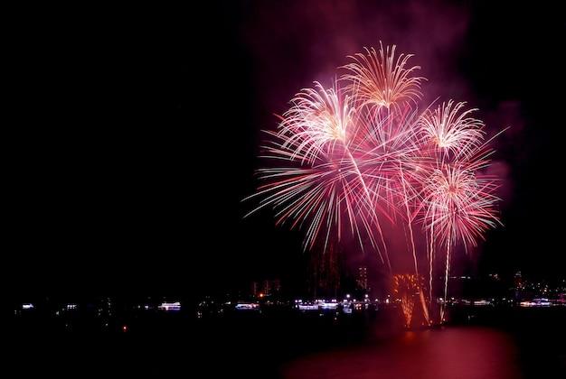 Stupendi fuochi d'artificio che sguazzano nel cielo notturno sopra il porto della città