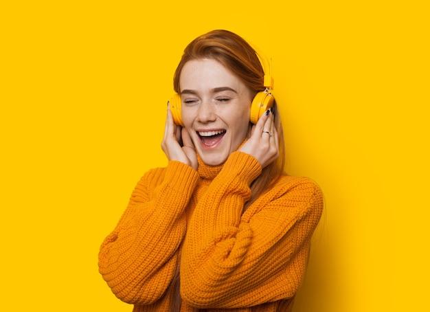Splendida signora caucasica allo zenzero sta ascoltando musica mentre indossa un maglione su una parete gialla con spazio di copia