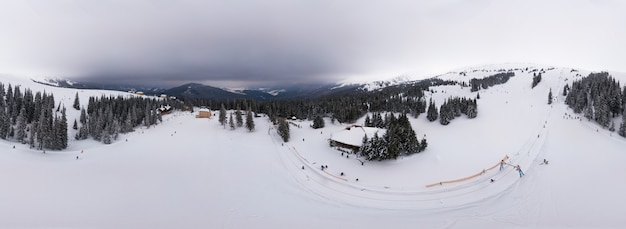 Panorama mozzafiato di dolci colline e montagne innevate con campi turistici in una giornata nuvolosa invernale