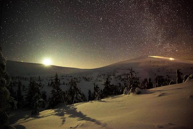 Splendido e pittoresco paesaggio invernale, colline e alberi innevati si stagliano contro il cielo stellato e il sole