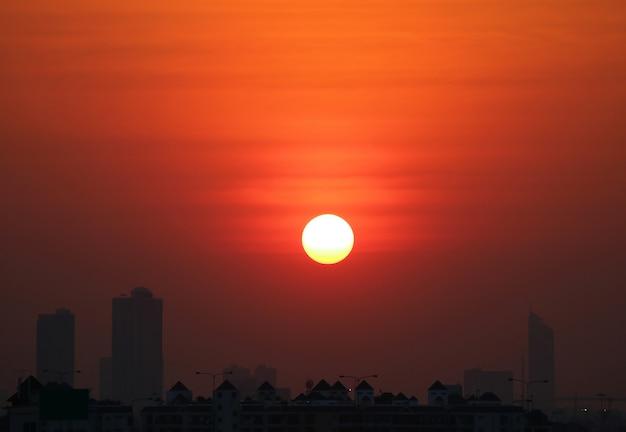 Tramonto sbalorditivo sul cielo arancio profondo di colore sopra gli alti edifici della siluetta, bangkok, tailandia