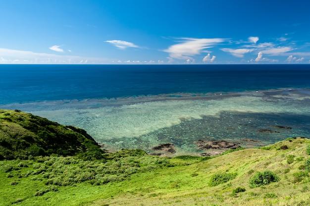 Splendida vista dall'alto di un oceano blu profondo pieno di barriere coralline rocce costiere erba verde isola ishigakiki