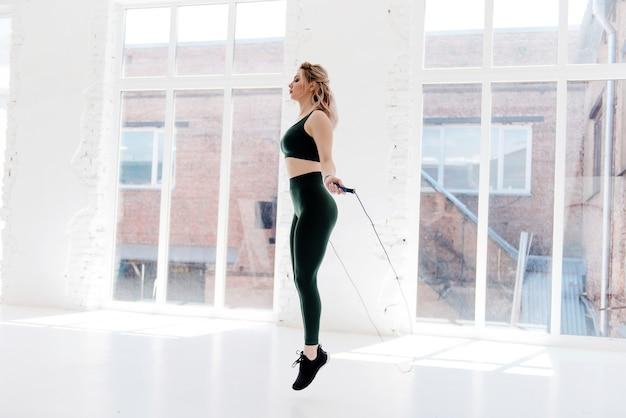 Splendida giovane donna in abbigliamento sportivo verde che salta da sola con la corda per saltare