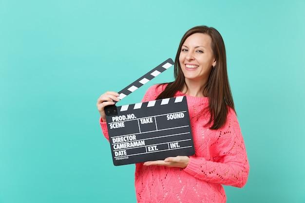 Splendida giovane donna in maglione rosa lavorato a maglia tenere in mano il classico film nero che fa ciak isolato su sfondo blu turchese, ritratto in studio. concetto di stile di vita della gente. mock up copia spazio.