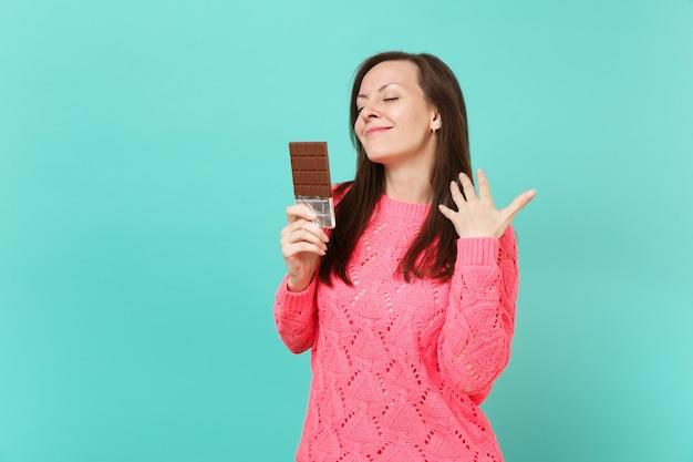 Splendida giovane donna in maglione rosa lavorato a maglia che tiene gli occhi chiusi, tiene in mano una barretta di cioccolato isolata su sfondo blu turchese parete, ritratto in studio. concetto di stile di vita della gente. mock up copia spazio.