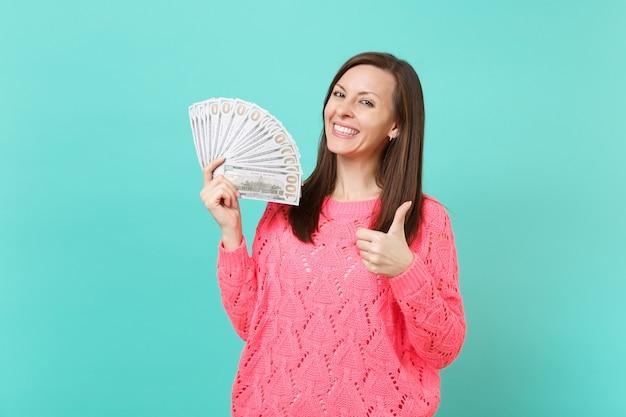 Splendida giovane donna in maglione rosa lavorato a maglia che mostra pollice in su, tiene in mano un sacco di banconote in dollari, denaro contante isolato su sfondo blu muro. concetto di stile di vita della gente. mock up copia spazio.