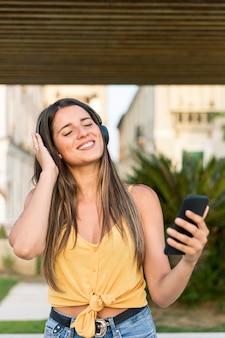 Giovane donna sbalorditiva che ascolta la musica all'aperto