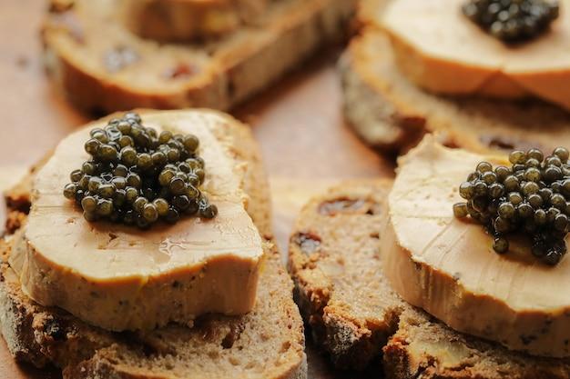 Caviale nero di storione su foie gras e pane da taglio, concetto di celebrazione fevtive