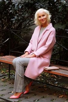 Stile donna bionda seduta sulla panchina, giornata autunnale.