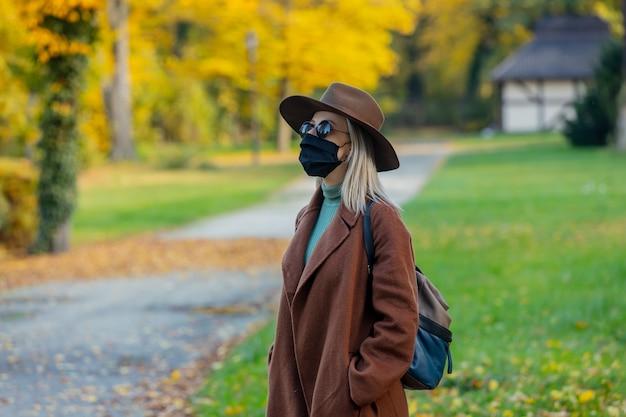 Stile bionda in maschera e cappotto in autunno parco con aceri