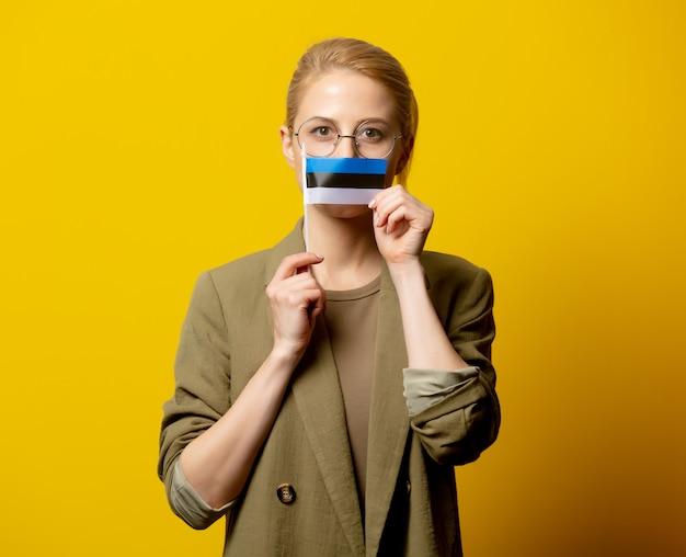 Disegni la donna bionda in rivestimento con la bandiera estone su giallo