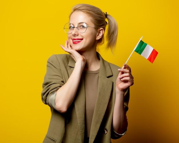 Stile donna bionda in giacca con bandiera italiana sul giallo
