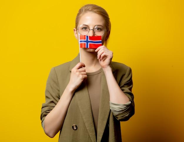 Stile donna bionda in giacca con bandiera norvegese su giallo