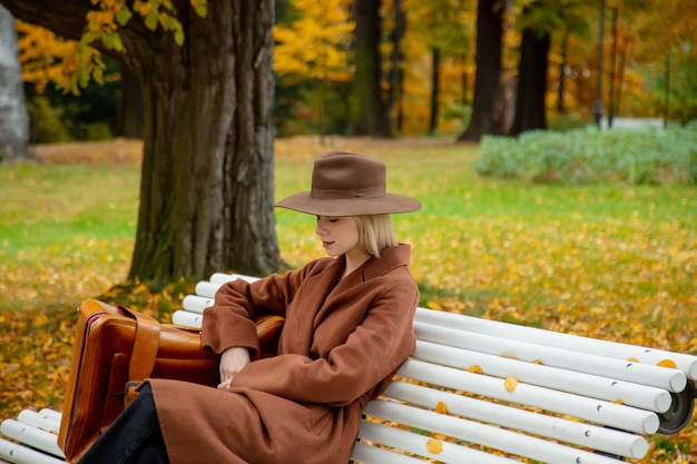 Ragazza di stile in cappotto marrone con la valigia che si siede su una panchina nel parco d'autunno
