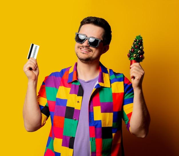Ragazzo in stile con camicia anni '90 e infradito con albero di natale