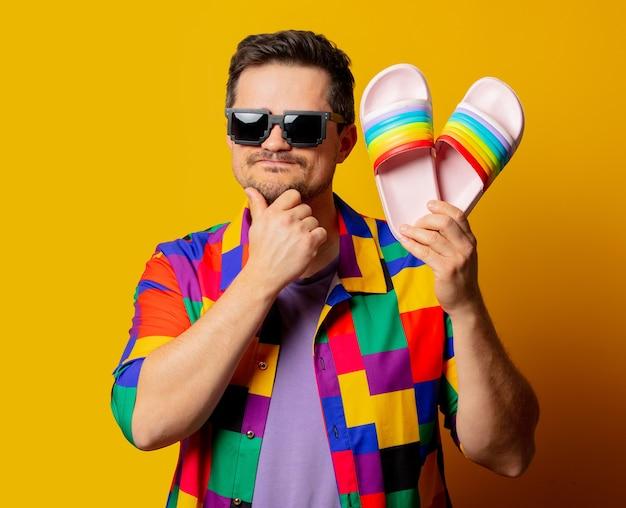Ragazzo di stile con camicia anni '90 e occhiali da sole pixel tiene le infradito