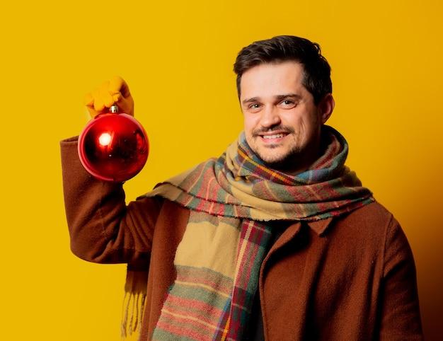 Uomo di stile in cappotto e sciarpa con pallina di natale