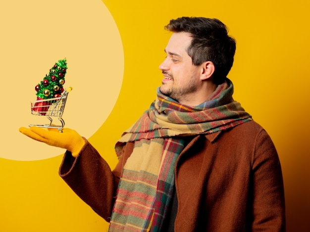 Stile uomo in cappotto e sciarpa con albero di natale all'interno di un carrello