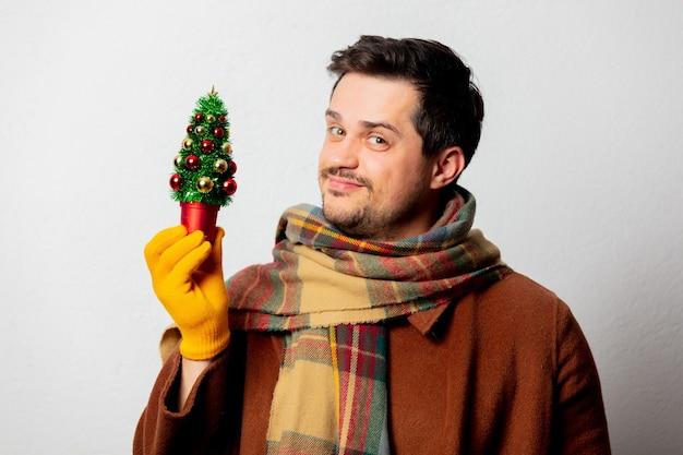 Uomo di stile in cappotto e sciarpa con albero di natale