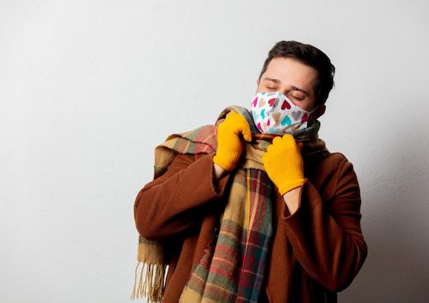 Uomo di stile in cappotto e sciarpa con maschera facciale