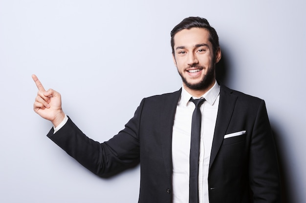 Stile e sorriso. ritratto di un giovane fiducioso in abiti da cerimonia che guarda la telecamera e punta lontano mentre si trova in piedi su uno sfondo grigio