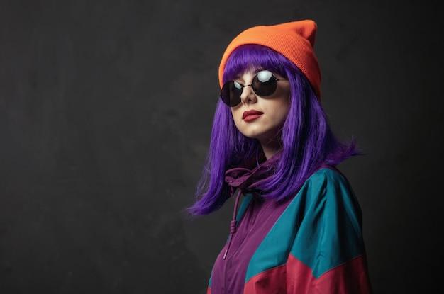 Stile donna in occhiali e tuta sportiva anni '80 sul muro grigio