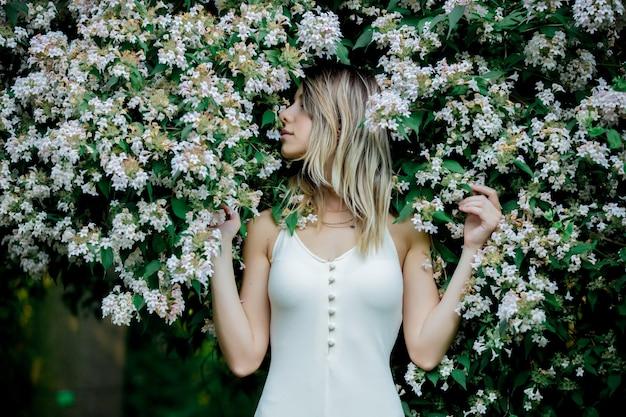 Stile donna vicino all'albero in fiore in un giardino in primavera