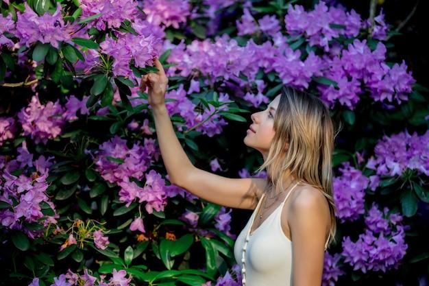 Stile donna vicino ai fiori di rododendro in un giardino in primavera