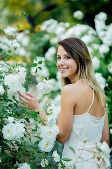 Stile donna vicino a rose bianche in un giardino in primavera