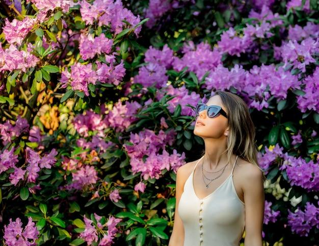 Stile donna in occhiali da sole vicino ai fiori di rododendro in un giardino in primavera