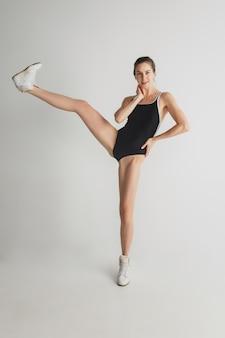 In stile. bella giovane donna isolata su sfondo grigio studio. divertirsi, felice, a figura intera. ballare, diventare pazzo, divertirsi. ragazza alla moda in costume da bagno sportivo nero. copyspace.