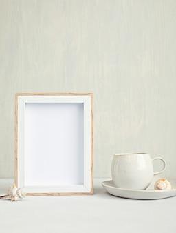 Desktop minimal in stile con cancelleria di colore organico, tazza di caffè, cornice