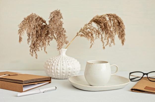 Desktop minimal in stile con stazionario di colore organico, tazza di caffè