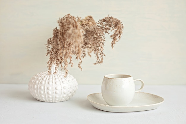 Tavolo minimal in stile con tazza da caffè in colore organico e vaso con erbe essiccate