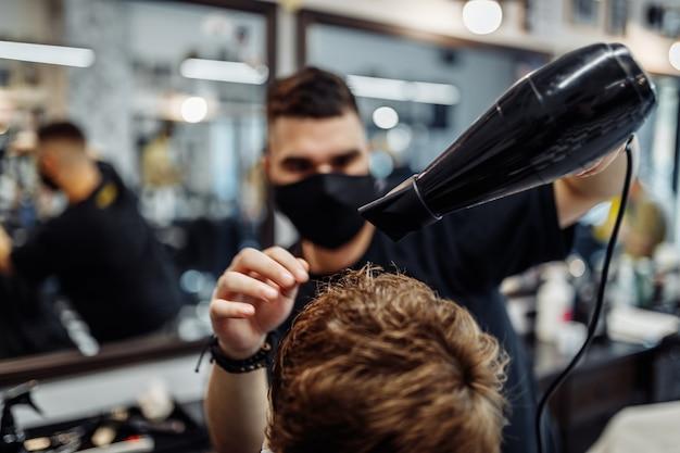 Acconciatura dei capelli degli uomini. il barbiere fa un'acconciatura alla moda. stile di vita in un barbiere.