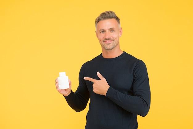 Lo styling dei capelli dovrebbe essere semplice. uomo felice punta il dito su sfondo giallo bottiglia. shampoo e condizionante. parrucchiere. barbiere. toelettatura maschile. la cura dei capelli dovrebbe essere la tua prima priorità.