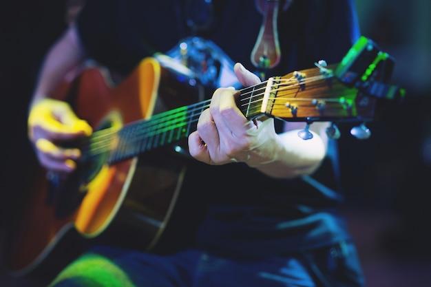 Chitarra acustica elegante che suona a mano. artista
