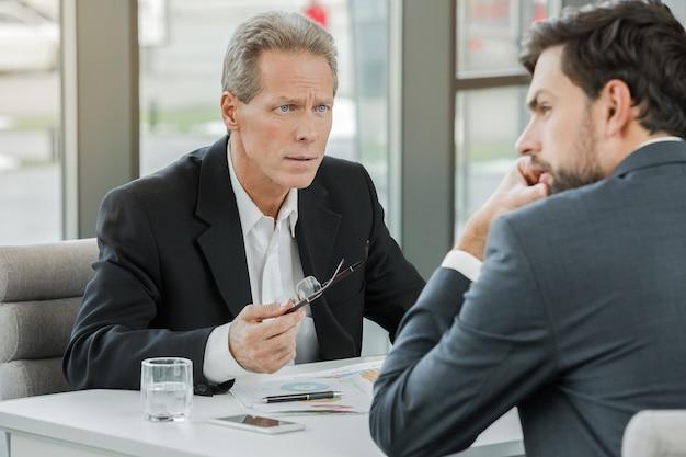 Eleganti uomini d'affari adulti durante la giornata lavorativa in ufficio. uomini d'affari che discutono seriamente del piano. interno dell'ufficio con grande finestra