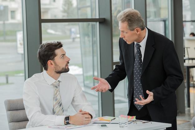 Eleganti uomini d'affari adulti durante la giornata lavorativa in ufficio. uomini d'affari che lavorano con i documenti. interno dell'ufficio con grande finestra