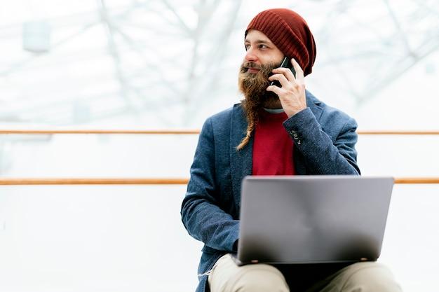 Elegante uomo hipster adulto con cappello e giacca con barba intrecciata che parla al telefono e usa il laptop al chiuso