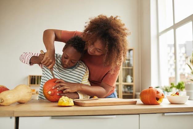Elegante donna afroamericana trascorrere del tempo con suo figlio in piedi al tavolo intagliare la zucca per halloween con un coltello da cucina insieme