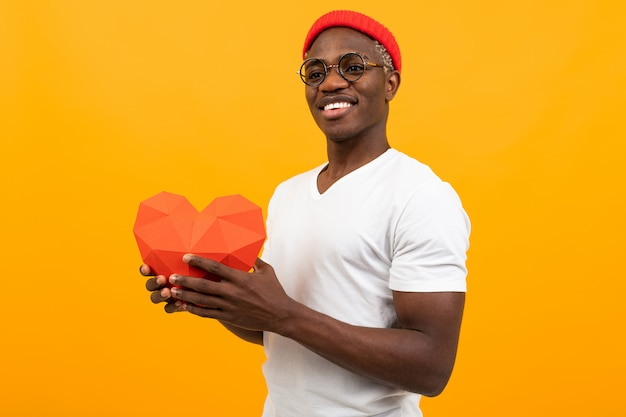 L'elegante uomo africano con un bel sorriso bianco come la neve in una maglietta bianca tiene in mano un mock-up 3d rosso di un cuore di carta per san valentino e guarda lateralmente lo studio giallo