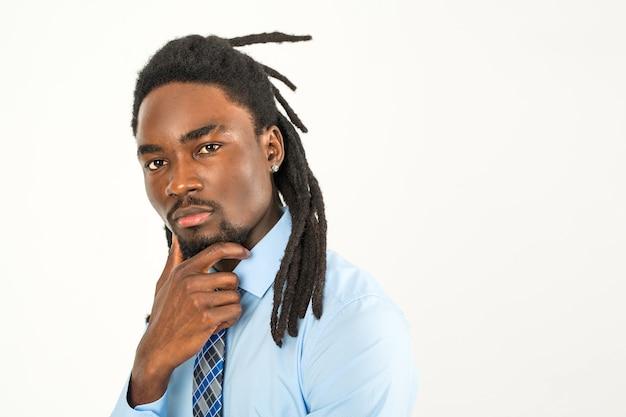 Elegante uomo africano con i dreadlocks in una camicia su uno sfondo bianco