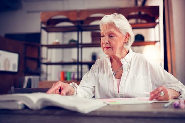 Signora invecchiata alla moda. elegante signora anziana con rughe facciali seduta a tavola e leggendo un libro pur avendo tempo libero