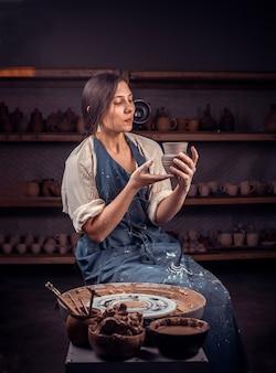 Elegante donna artigiana posa sul banco con ruota di ceramica e rendendo pentola di terracotta