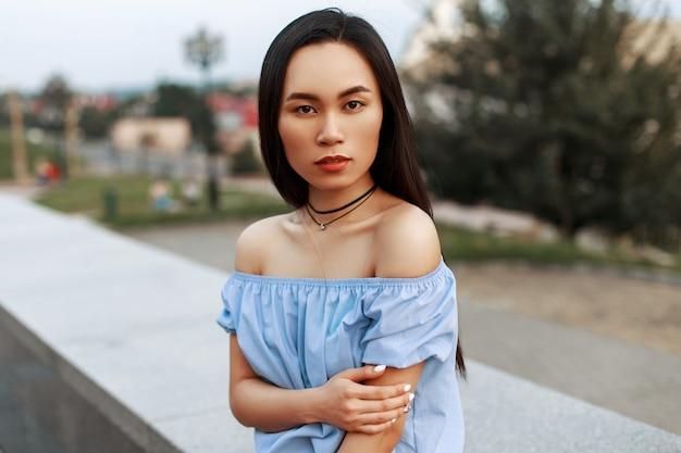 Bella ragazza asiatica alla moda in camicetta blu in posa sulla città.