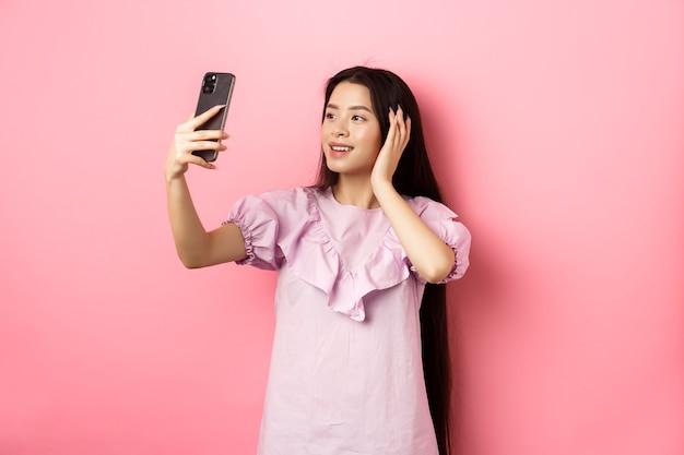 Elegante ragazza asiatica blogger prendendo selfie sul telefono cellulare, in posa per la foto dello smartphone, in piedi in abito su sfondo rosa.