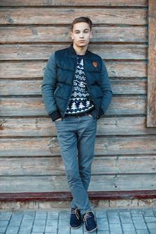 Ragazzo attraente alla moda con un'acconciatura alla moda con una giacca alla moda in un maglione lavorato a maglia blu in jeans alla moda con stivali invernali si trova vicino a un muro vintage in legno all'aperto. bravo ragazzo.