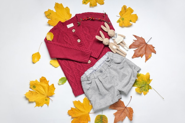 Vestiti alla moda del bambino di autunno con foglie e giocattoli sulla superficie bianca