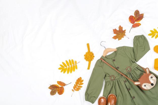 Elegante set autunnale di vestiti per bambini. abito verde, borsa marrone, scarpe e collant gialli, accessori per capelli e foglie autunnali su sfondo bianco. concetto di lookbook della ragazza di moda. vista dall'alto copia spazio.